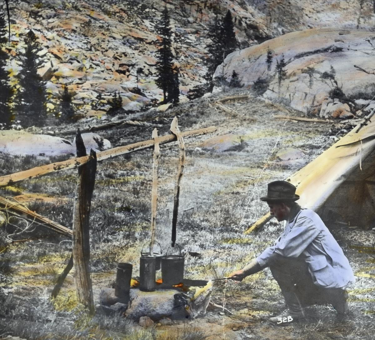 """Håndkolorert dias. En mann passer bålet, der to kjeler koker. Bak skimtes delene av et telt og et steinete fjellandskap. I boken """"En emigrants ungdomserindringer"""" forteller fotografen Anders Beer Wilse om sitt arbeid i U.S.A."""
