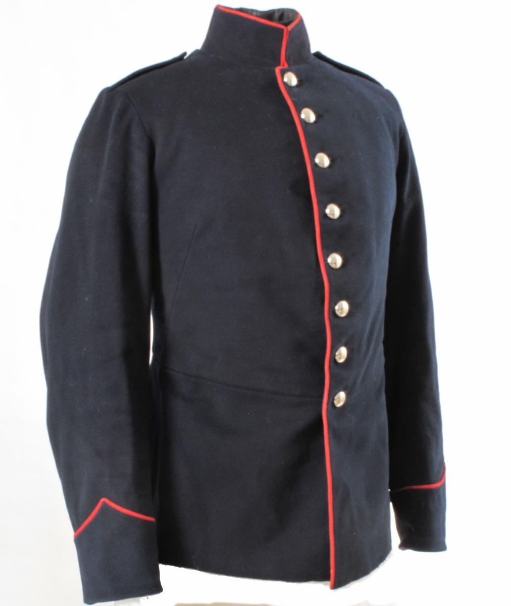 """Uniformsjakke, i marineblått klede, røde passepoils, enkeltknappet med 8 glatte """"sølv"""" knapper, opprettstående,  høy krave, skulderklaffer, oppslag med rød  passepoil på ermet (menig uniform). Falske skjøter med  klaffer med røde passepoils, og 6 knapper i ryggen.  Sterkt stoppet  i brystet. Innv. foret med smalstripet sort  bomullstoff."""