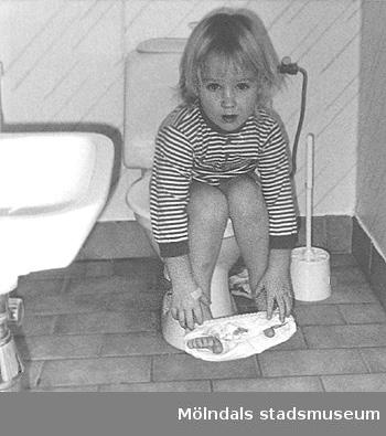 Ett barn sitter på toaletten i väntan på hjälp. Bild tagen till Mölndals museums utställning 1993 om och av daghemmet.