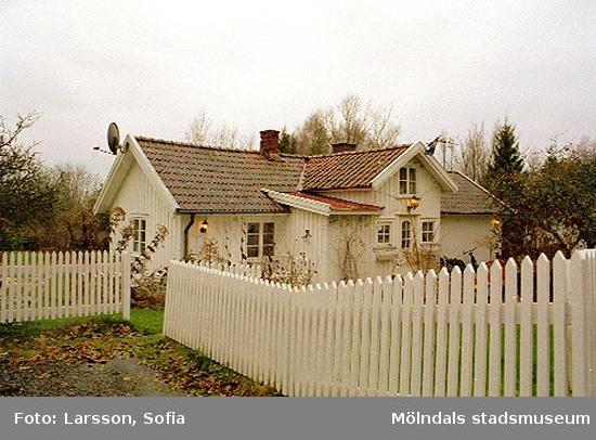 Bostadshus omgärdat av vitt staket.