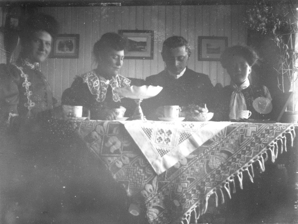 I Badderen i Kvænangen kommune (i Troms). Hanna Kjeldsberg, fru Leithe (fornavn Johanna?), Tøllef M. Nilsen Leithe (som var lærer i Kvænangen i en årrekke) og  Astrid Kjeldsberg. Kvinnene er kledd i dekorative kjoler.