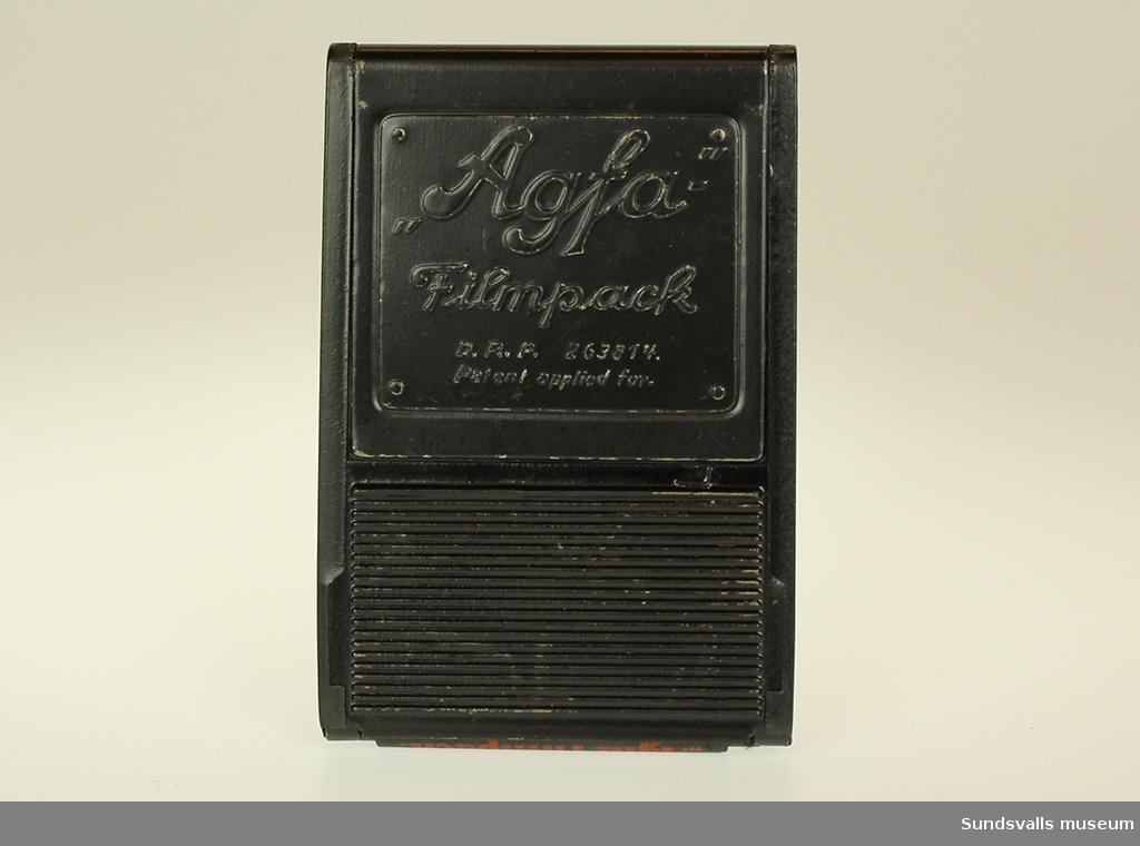 En svart metallhållare för film. Innehåller 7 stycken numrerade negativ. Inslagen i svart och rött papper.