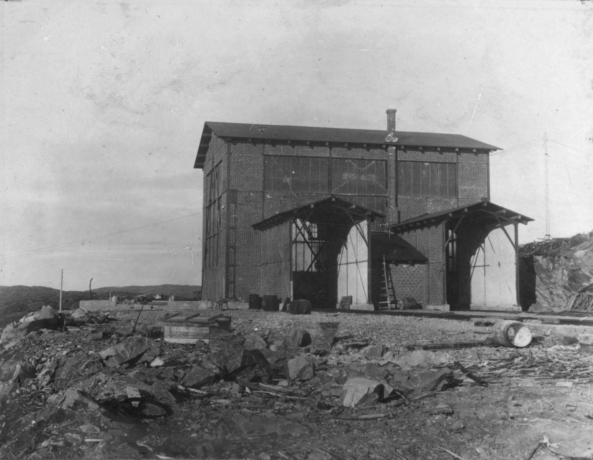 """Denne stod ferdig i 1910 da det første malmsettet gikk til Kirkenes. I dag kaller vi den for """"Gammelknusern"""". Den står enda i 2010, men noe redusert da den ikke har vært i bruk på lenge. I fra drifta startet opp etter krigen, da med en ny knuser på et annet sted i gruva, har denne blitt brukt til å knuse pukk. Det ble så bygget nytt Pukkverk neden for denne, der Knuservannet ligger (lå).  (Bildeopplysninger av Kurt Røst, oktober 2010). Kurt Røst skriver tillegg: """"Jeg har sjøl på 60 tallet sittet på """"Rossen"""" i mye støv, under pukknusing""""."""