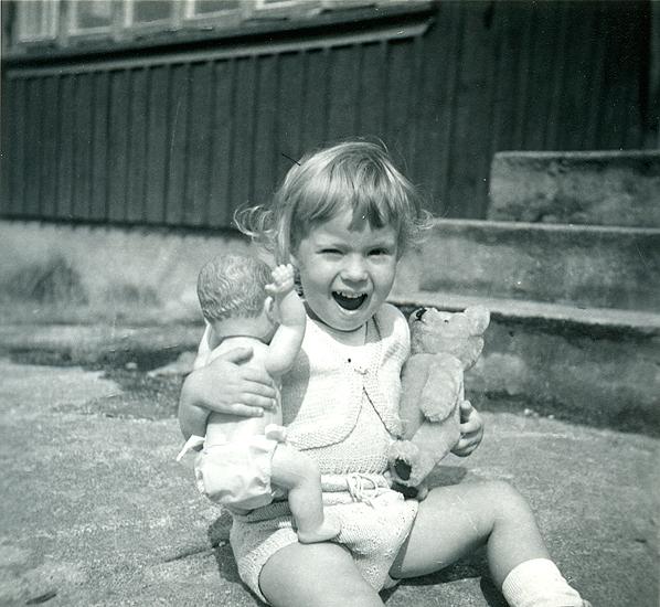 """Sommaren 1955. Veronika med liten babydocka och nalle som har hållit sig fin. Sparkbyxa och bolero stickad av Birgit i tunt bomullsgarn""""."""