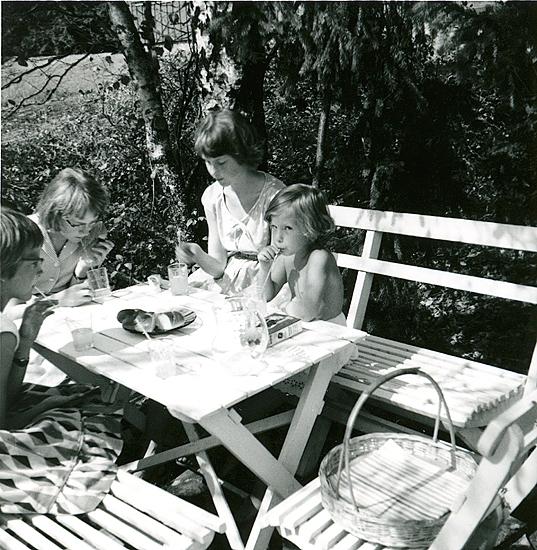 Saft i bersån, nu igenvuxen. Britta Molin, Ann Madgård, Karin Molin som var barnkär och skulle lära sig sällskapsdans. Obs. slät kardemummakrans från bageriet på bordet. Mormor köpte alltid det. Birgit och Gunnel fortsatte traditionen. Jag föredrog bulle med socker och gul kräm. Getingar samlades i bageriet och i vår berså.