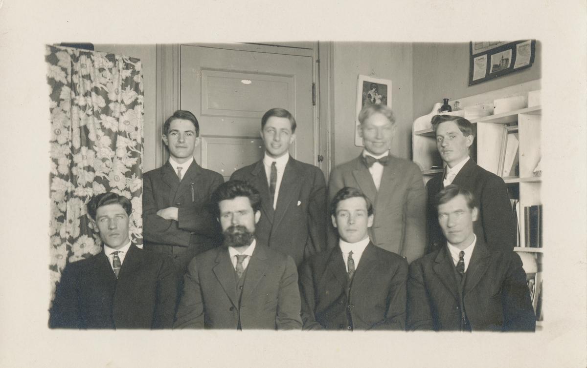 Gruppefotografi av åtte menn inne i et rom.