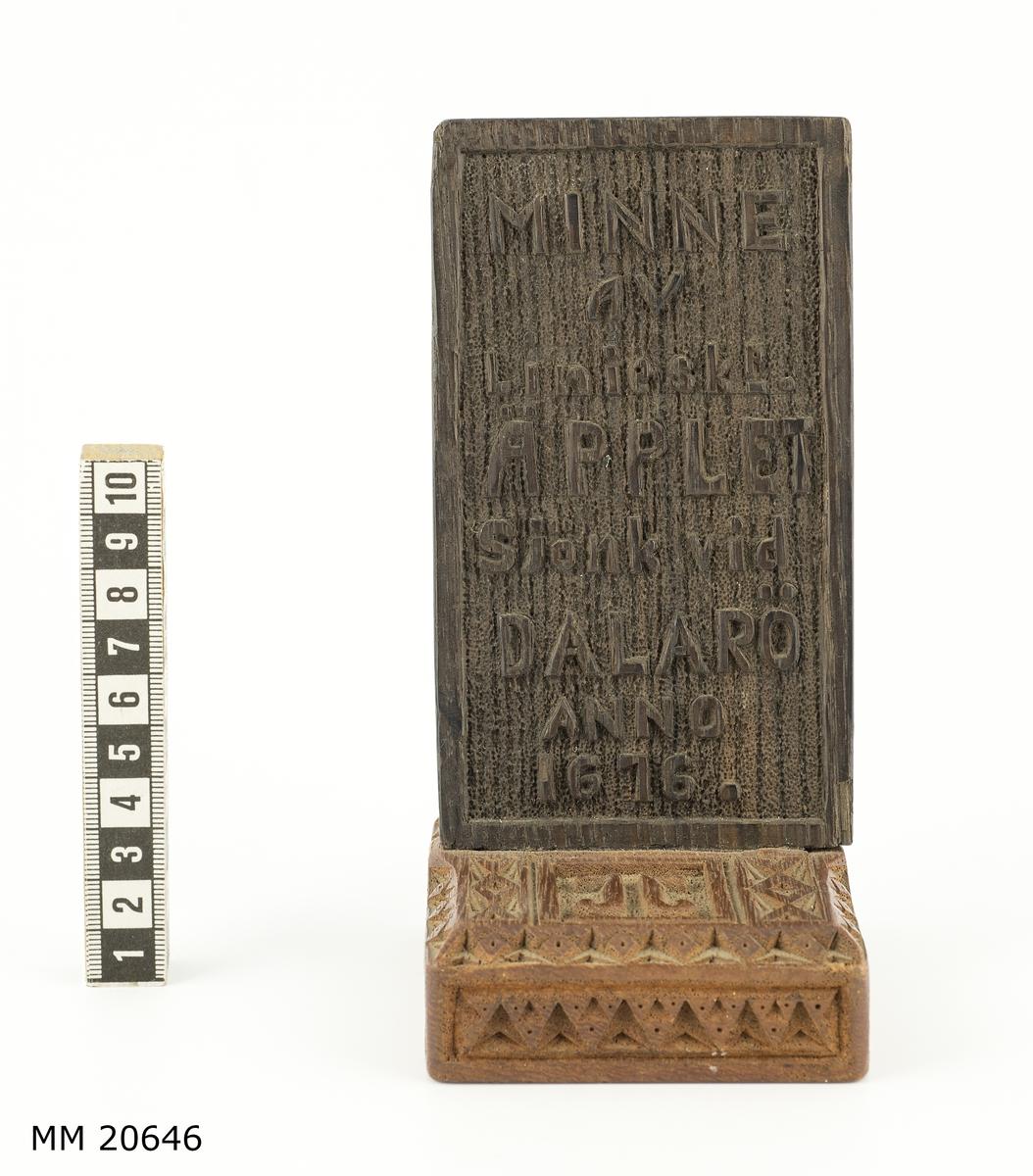 """Minnesplatta av ek, rektangulär, monterad på teakplatta. Försedd med skuren text, förhöjd relief: 'Minne av linjeskp. Äpplet sjönk vid  Dalarö Anno 1676."""" På baksida 'Gåva av (monogram) 1928"""". Teakplattan ornerad samt försedd med monogram: 'JJ"""". På baksida nedsänkt lapp med text: 'Teakträ tillhört inredningen till korvetten Chapmans kajuta. V.S."""" samt ritning av ett litet hus.  Saknar nummer i Westerbergs register."""