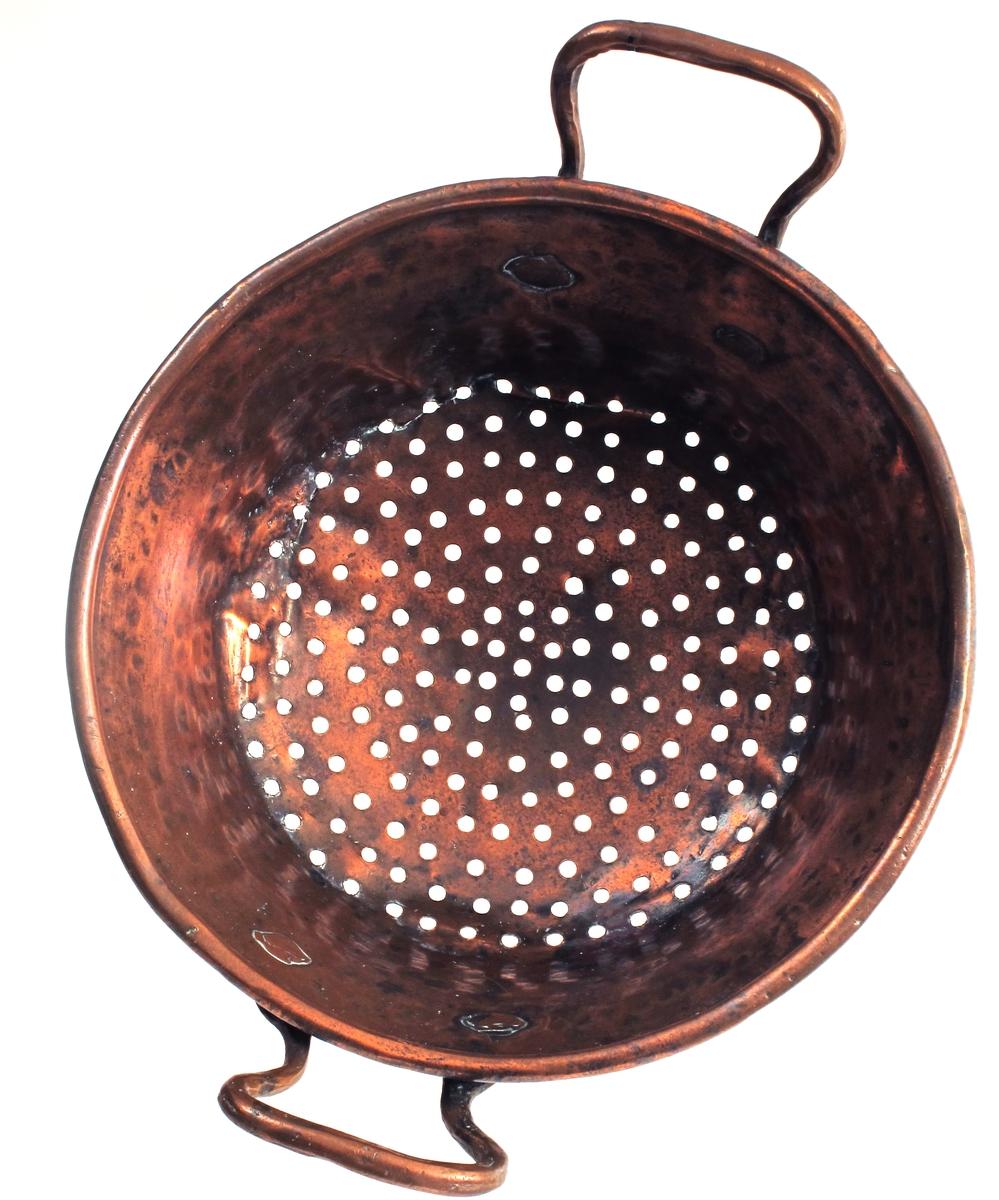 Dørslag, av kobber. Skålform med litt skrå sider, huller i bunnen, rundet brem, to  oppstående  hanker.   Utvendig i siden innrisset: M.V.N.   M.B.D. 1647.