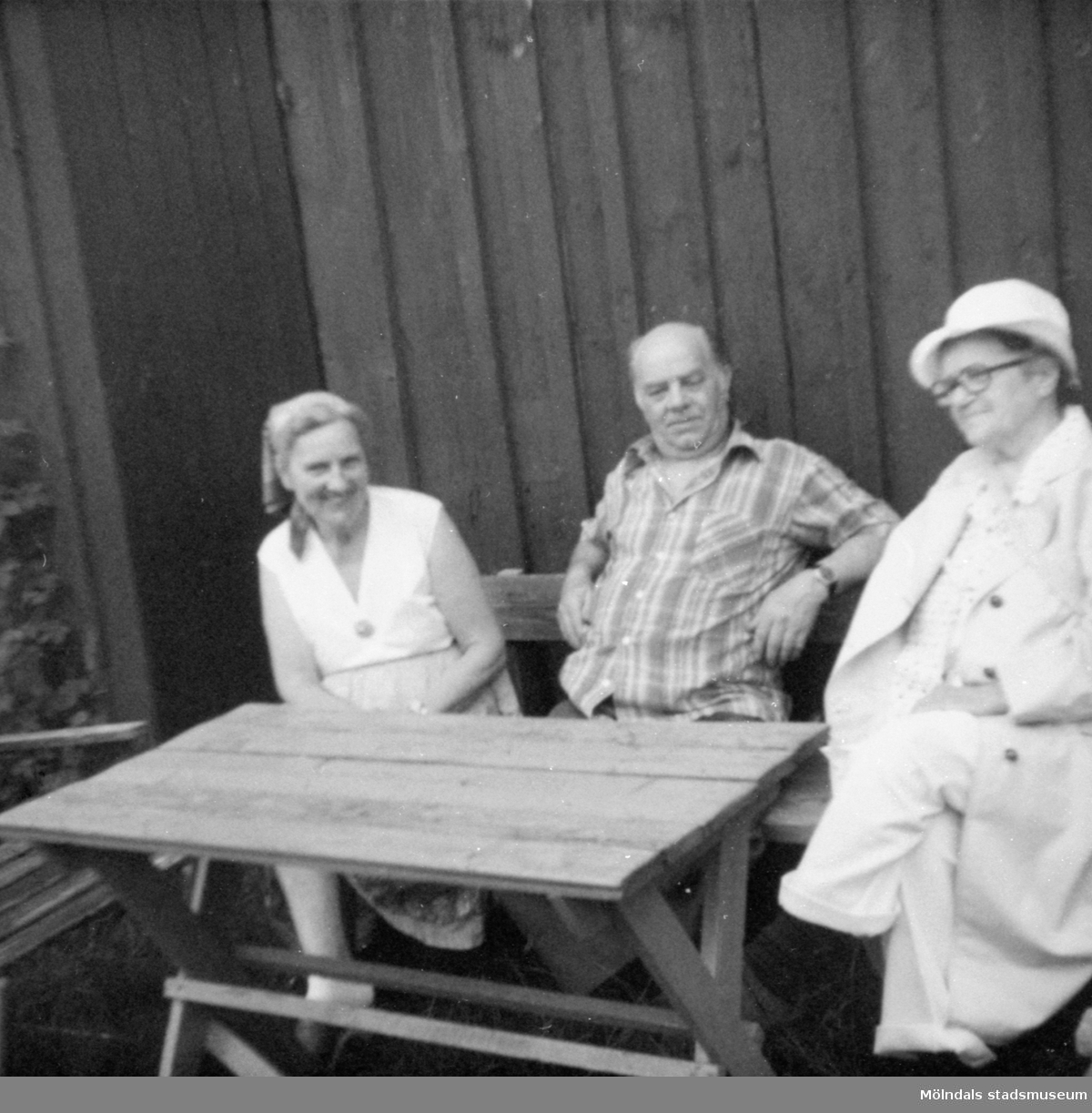 """Till höger sitter Anna """"ve sjön"""" (Anna Johansson) vid ett bord utomhus. Bredvid henne sitter hennes kusin och dennes hustru. Anna arbetade som husa på Gunnebo slott. Gunnebo 1979."""