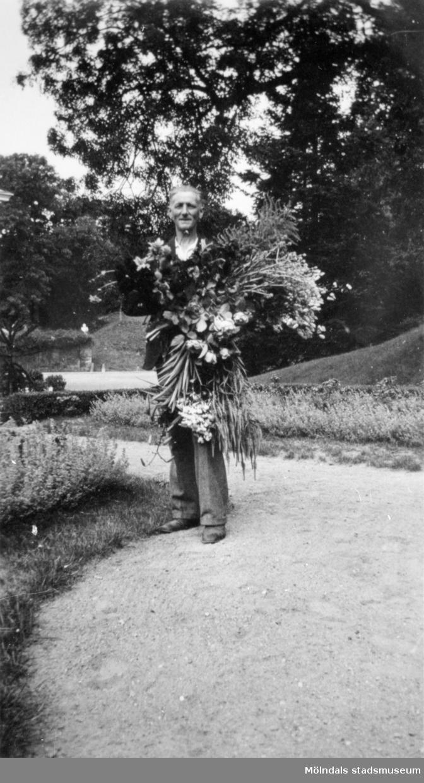 Charles Gunnehed (född Johansson) bär ett fång med blommor.Troligtvis arbetade han på Gunnebo slott. Gunnebo slottspark 1930-tal.