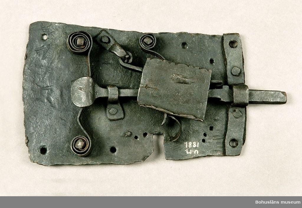 Ur handskrivna katalogen 1957-1958: Järnlås L. c:a 29 cm. Största Br. c:a 19 cm. Ålderdomlig typ. Nyckel saknas. Ngt. rostigt o defekt.