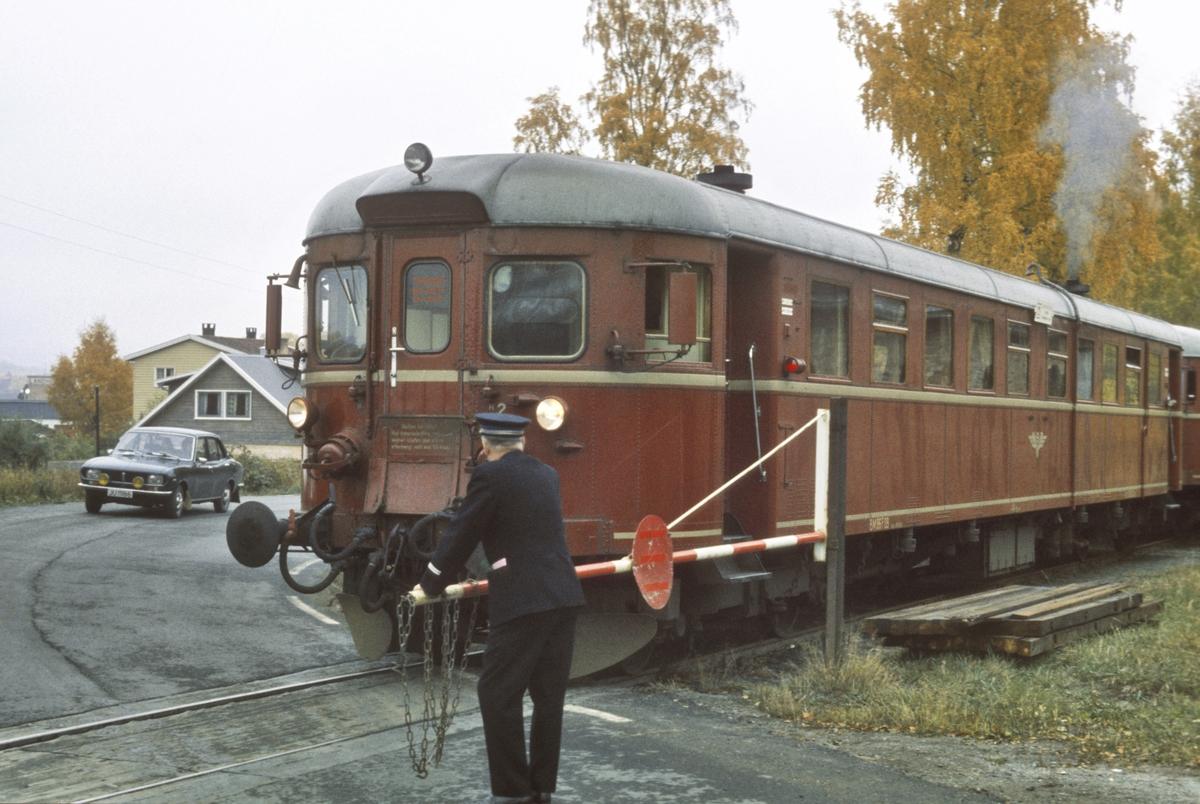 Ekstratog fra Skreia til Gjøvik passerer planovergangen ved Skreia stasjon. Togfører (overkonduktøren) betjener bommen.