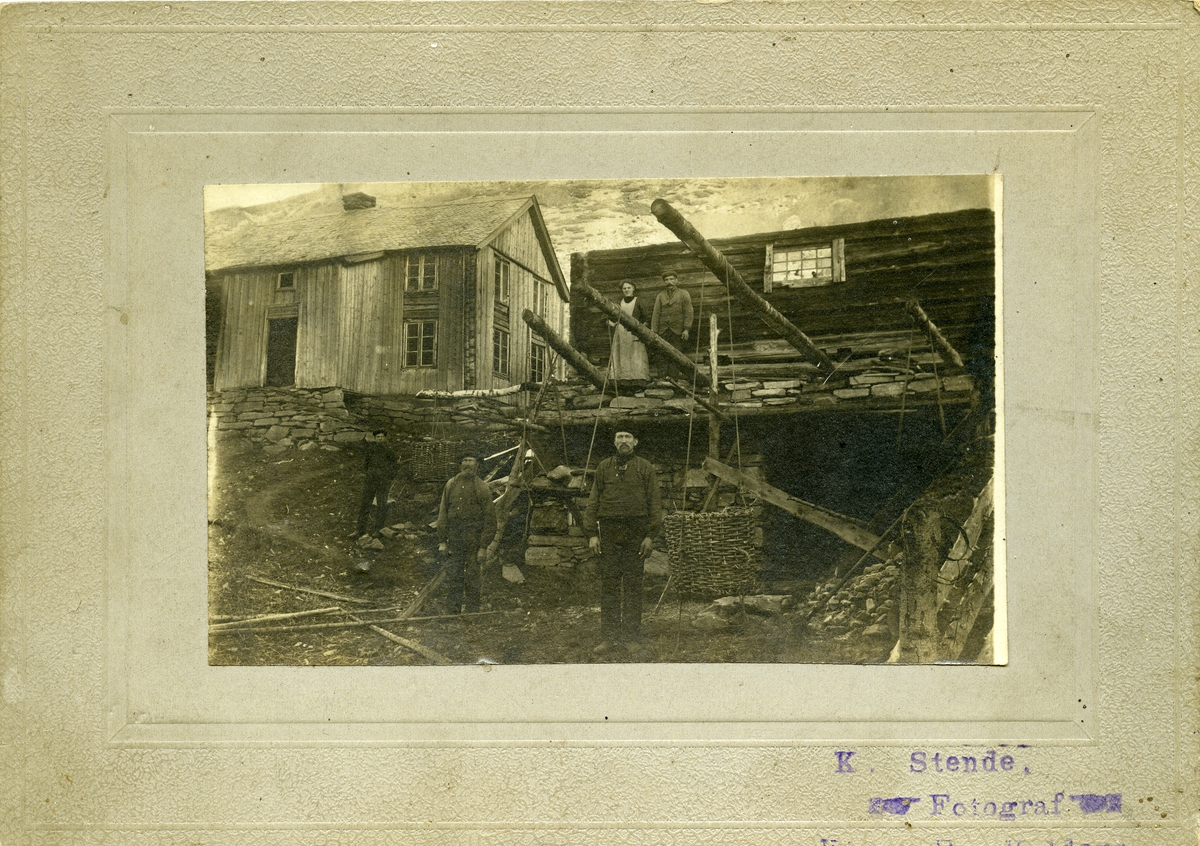 Bildet viser en gruppe mennesker foran trehusbebyggelse. Motivet kan antyde at det dreier seg om arbeidsfolk som har stilt seg opp foran arbeidet sitt.