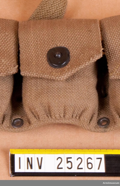 """Grupp C I. Ur uniform för manskap vid infanteri i Amerika. Består av vapenrock, byxor, damasker, hjälm, skor, fältflaska, patronbälte och väskor. Av tjockt bomullstyg, """"wibbing"""". Med lock. Stänges med järnknappar."""