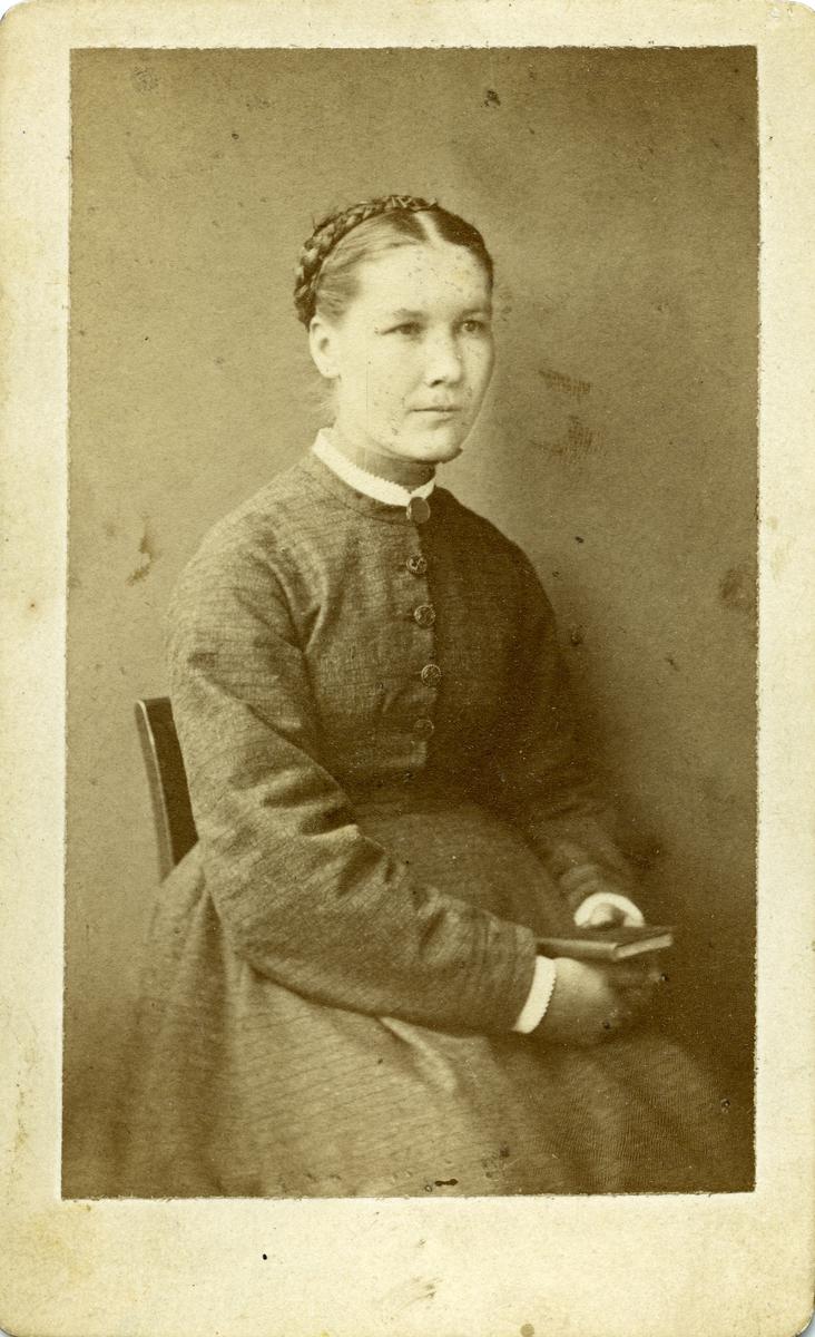 Portrett av kvinne på stol. Kvinnen er iført kjole og hun holder en bok i hendene. Kan være et mulig konfirmasjonsbilde.