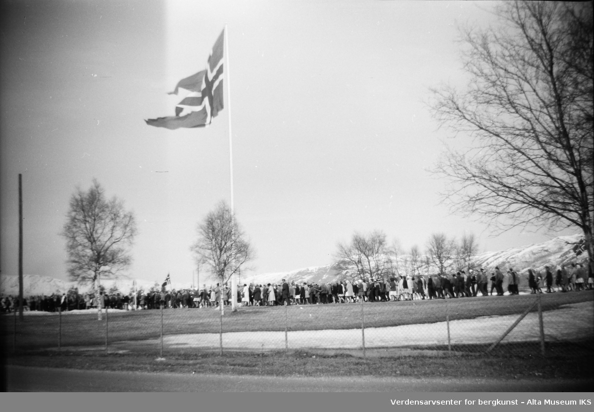 Et tog av mennesker går forbi en flaggstang på 17. mai. Et stort norsk flagg vaier i vinden fra toppen av flaggstangen.Bildet er tatt på våren 1962.