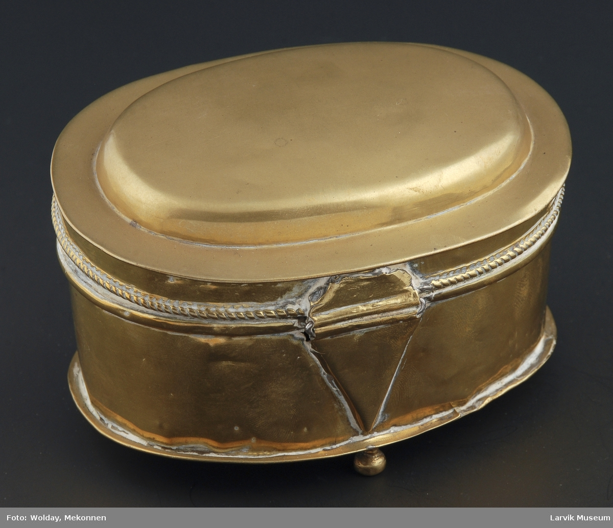 Form: oval eske på 3 små kuleben,lokk hengslet,enkel: vulst og profilering i sammenstøt lokk/eske innvendig fortinnet