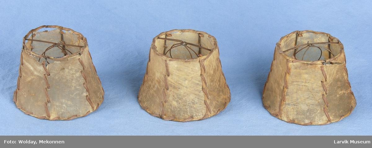 Form: Svakt innsvingt skjerm med bøyle for lyspære, trukket med tarmskinn.(sannsynligvis)