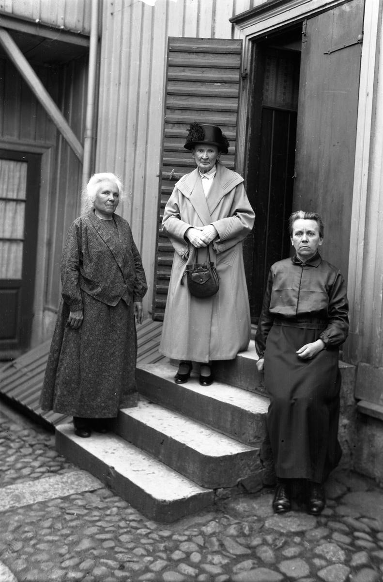 Tre äldre damer på en bakgård.