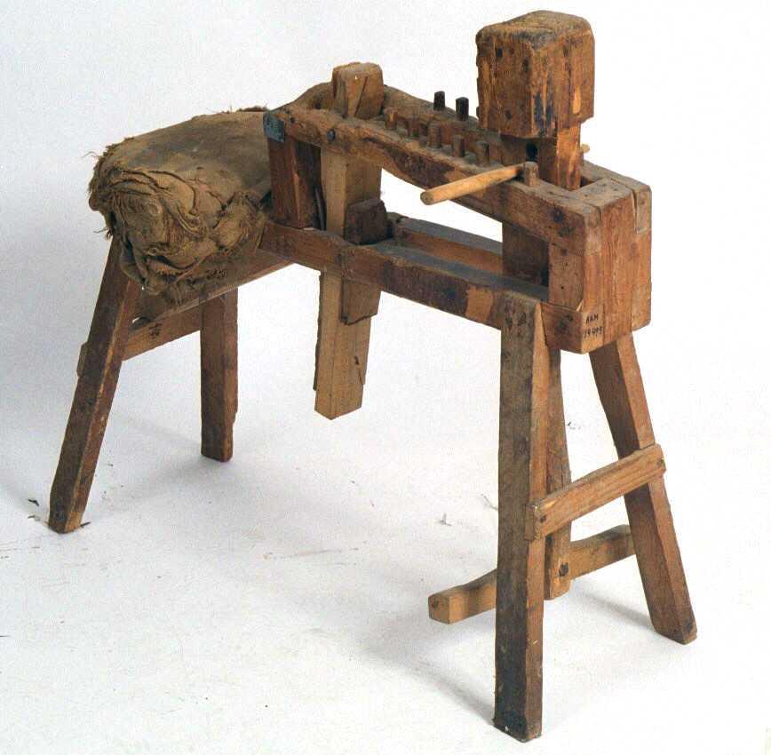 Arbeidskrakk for tresko. Furu, sete trukket med grov strie  Av form som en naglebenk, bare kortere, med  to skrått stilte  bukker med et stativ i sittehøyde.  I bakre del av dette et bredt halvsirkelformet  sete  trukket med flere lag sekkestrie. I fremre del er en ramme med to rekker oppståe6 i hver rekke, og en oppstående firkantet trekloss. synes å ha vært brukt som e ......