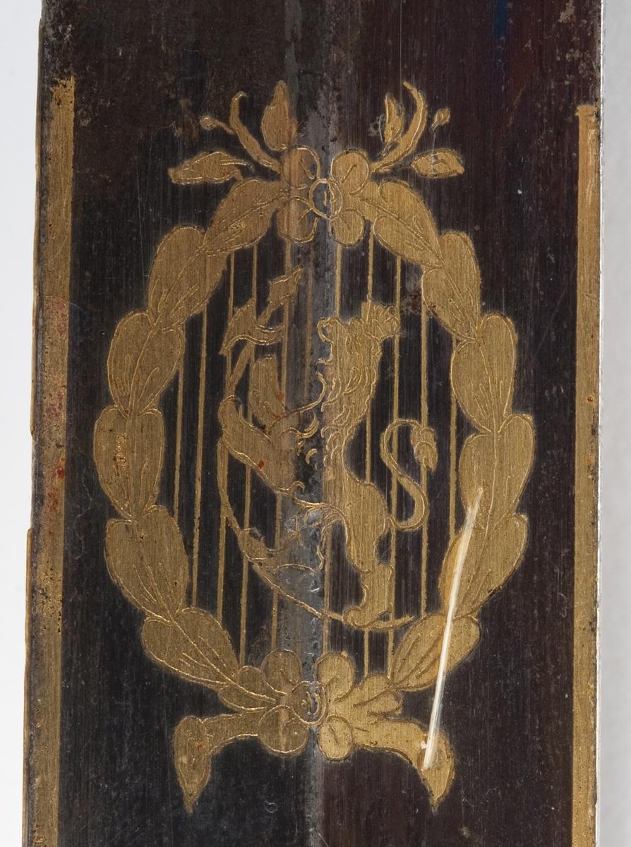 En kårde m/slire. Gallakårde efter O. E. Holck, stål m/messingbeslag, skjeftet m/løveh. dekorert med Carl Johan XIV's riksvåpen og løve, hengslet parerplate.  1. repr. Bergenhuiske infanteriregiment.