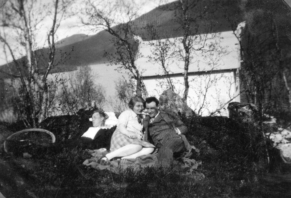 Kvinne og to menn ved Steinsåsvatnet. Sykkel til venstre.