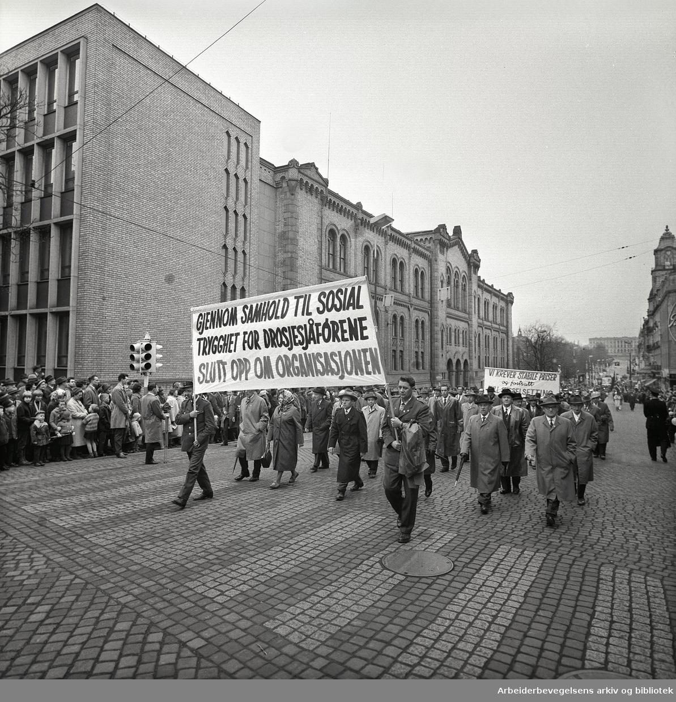 1. mai 1963 i Oslo.Demonstrasjonstoget i Karl Johans gate..Parole : Gjennom samhold til sosial trygghet for drosjesjåførene.Slutt opp om organisasjonen.Parole: Vi krever stabile priser og fortsatt full sysselsetting