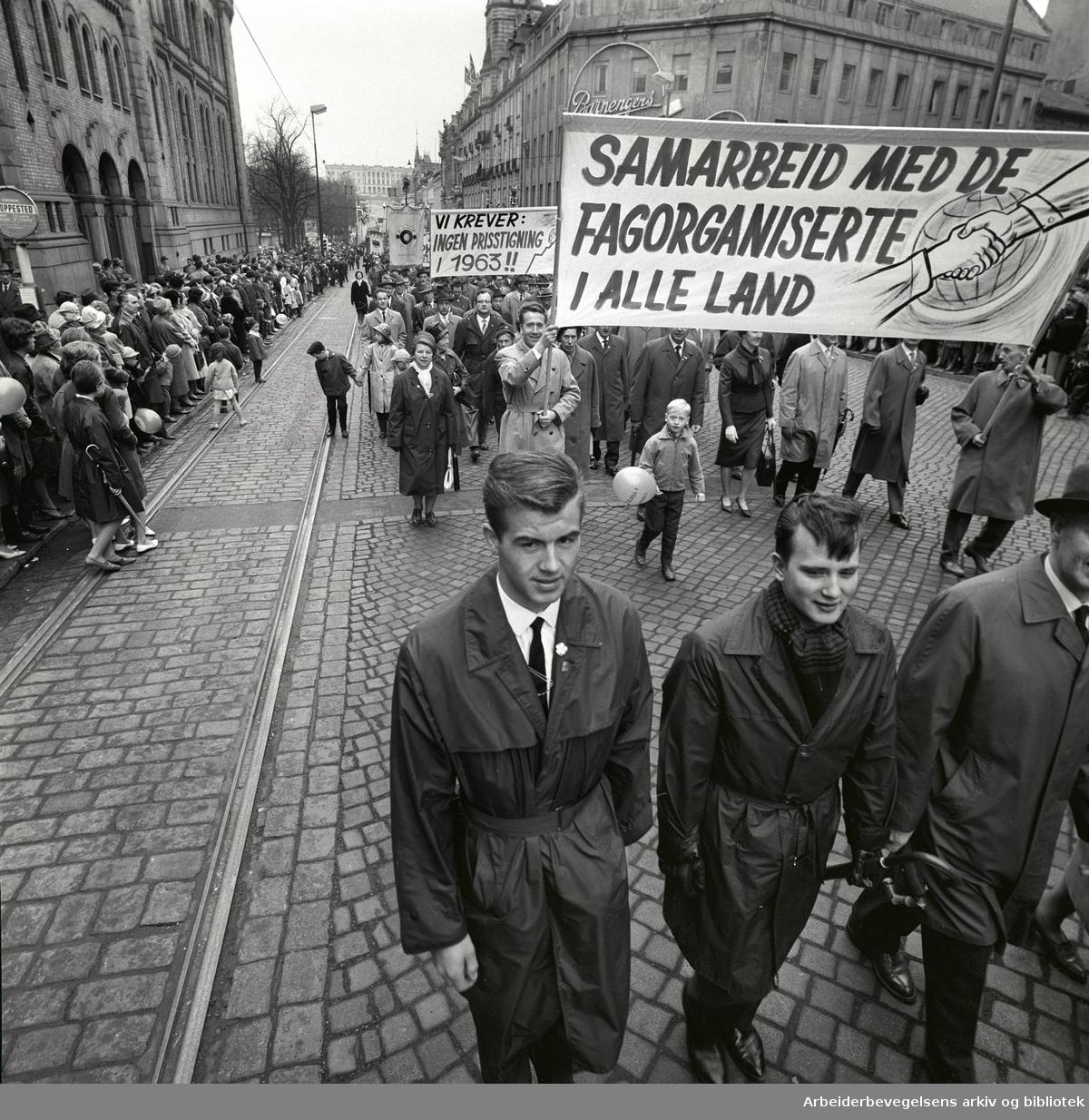 1. mai 1963 i Oslo.Demonstrasjonstoget i Karl Johans gate..Parole : Samarbeid med de fagorganiserte i alle land.Parole : Vi krever: Ingen prisstigning i 1963