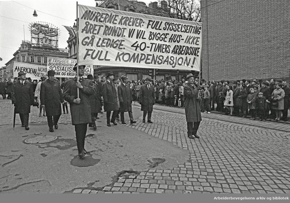 1. mai 1969 i Oslo.Demonstrasjonstoget i Karl Johans gate.Parole: Murerne krever: Full sysselsetting året rundt. Vi vil bygge hus- ikke gå ledige. 40-timers arbeidsuke..Full kompensasjon!