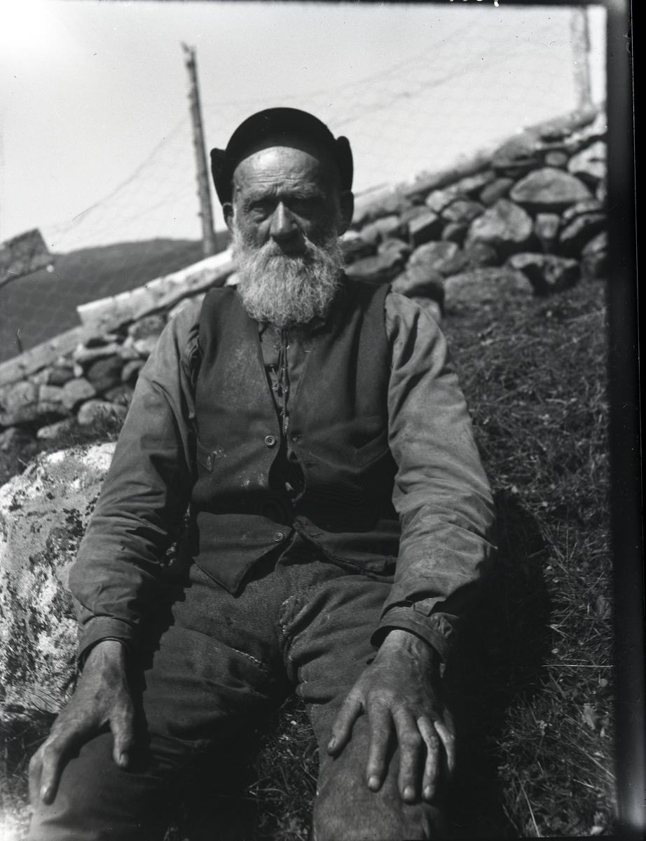 Mann som sitter på grasbakken foran en steinmur. Han har hvitt skjegg og er iført arbeidsklær; skjorte med snøring, vest og en lue/hatt på hodet.