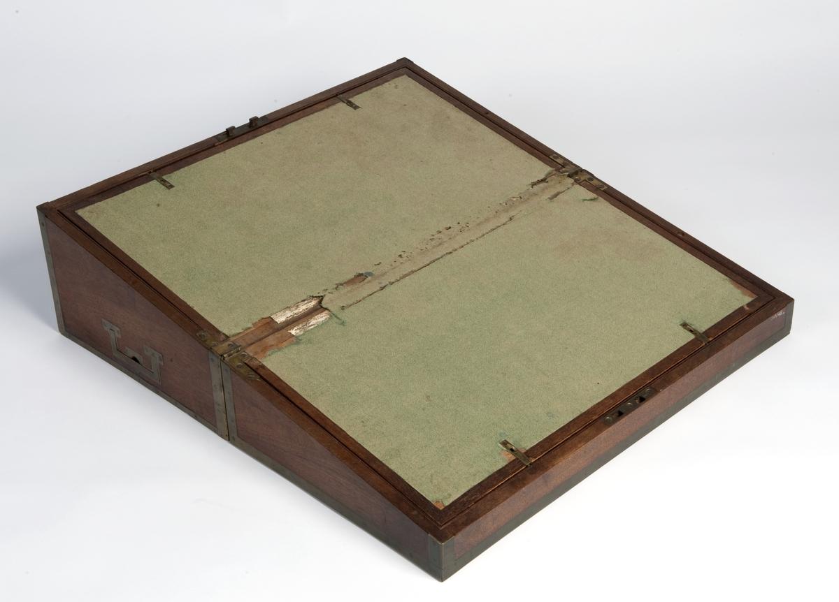 1 reiseskriveskrin i mahogny, m messingbeslag. Skriveplate trukket med grønt klede. Skrinet har spesialtilpassede rom til bl.a. et teservise fra Wedgewood, et lite speil m.m.