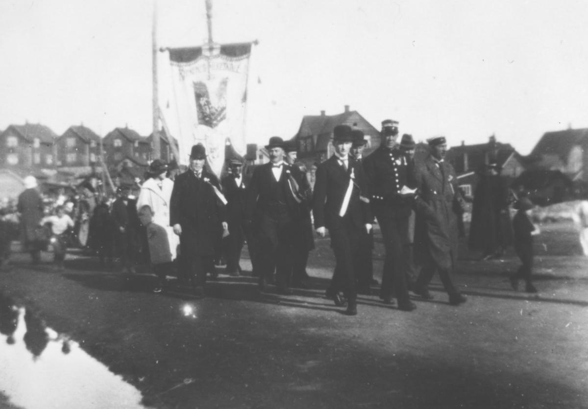 17.Mai i Kirkenes. Barnetoget passerer her Kirkegaten ved kirken. Vi ser menn i dress og uniformer, og fanen til Kirkenes fylkesskole.