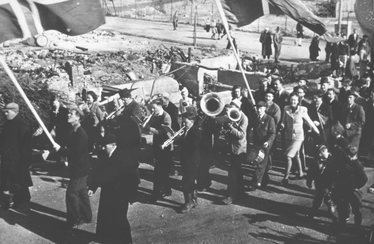 17. mai-tog i Kirkenes etter krigen. Et lite korps med trompeter, horn og tromme etterfulgt av smilende mennesker. I bakgrunnen ser vi ruiner etter bombinga.