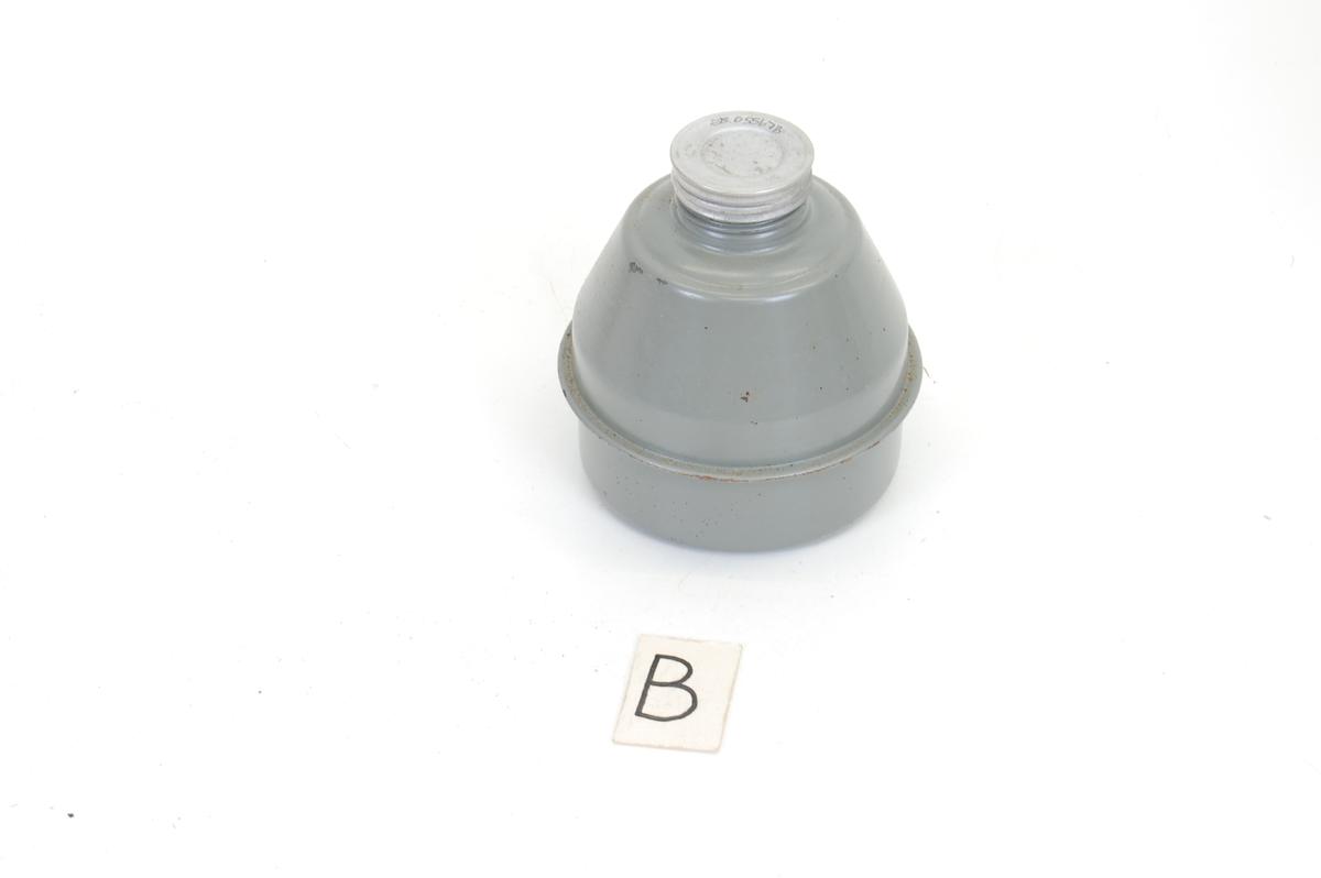 Betegnelse: gassmaske med bruksanvisning og ekstra brilleglass i hylse Form: hylsteret har sylinderform med vannrette striper i form av bulker ut, lokket er løst, men forsvinner ikke for det er tredd på et bånd som sitter fast i selve hylsen. Gassmasken ser ut som et innsekt, med runde øyenhull med plastbriller i og en svart snute hvor en skal feste en grå kolbe. Tilstand: endel rust på hylsteret, resten i ganske god stand. Gummien i masken er litt sprukket rett ved snuten, men ikke mer enn at jeg tror den ville vært brukbar dersom det var nødvendig.  På kolben er det bare bittelittegrann rust. Den lille papirposen med ekstra brilleglass (eller hva det er) er gulnet og sprø, men hel. Bruksanvisningen er litt sprø og har noen flekker av rust og gulnet noe.