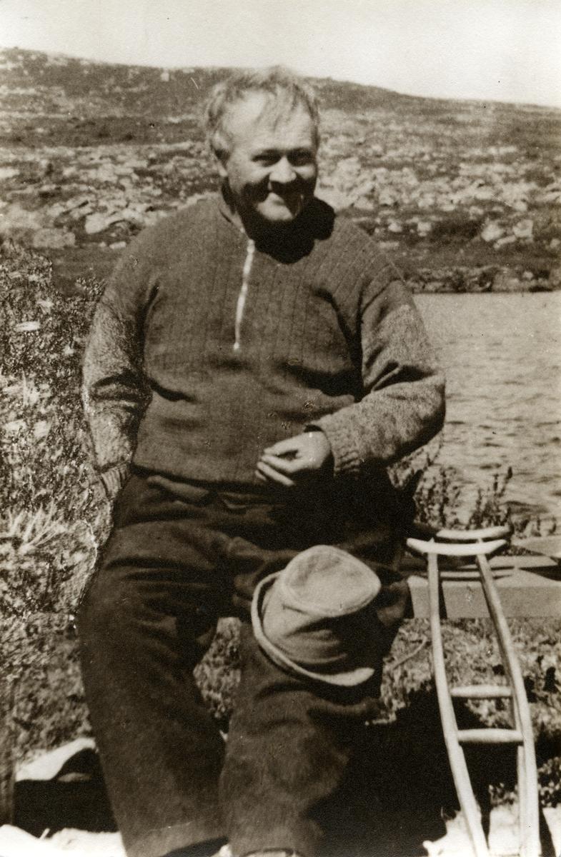 Portrett av en mann sittende på en benk. Mannen har en hatt på kneet og en krykke plassert ved siden av.