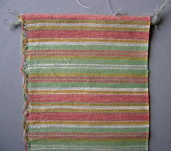 Vävprov, möbeltyg i bomull, lin och ull vävt i korskypert med inslagseffekt. Randigt i inslagsriktningen i grönt och rosa med smalare ränder i gult och grått/vitt. Varp i grått bomullsgarn nr 16/2. Inslag i lingarn nr 16/1 samt ullgarn; redgarn nr 20/2 och ibland lingarn nr 16/2 istället för dubbelt 1-trådigt lingarn. Tre trådar tillsammans per inslag; två trådar lingarn och en tråd ullgarn.