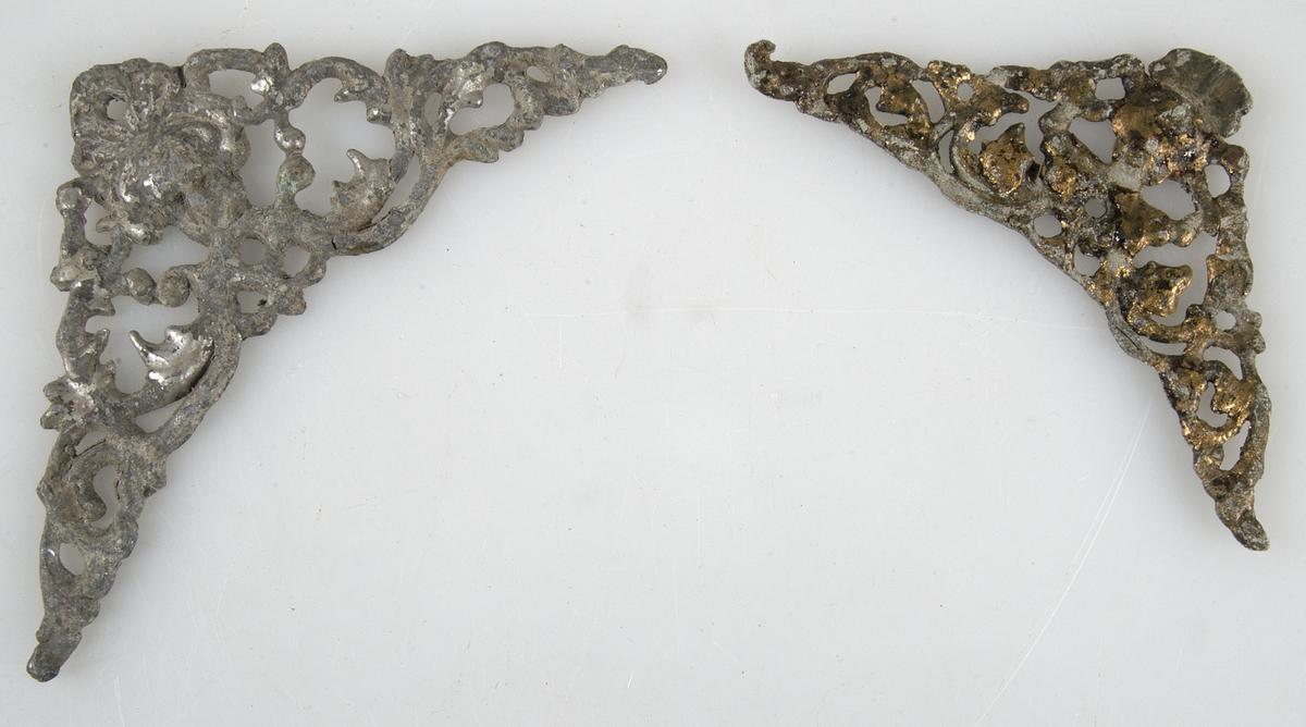 Två beslag av tenn, trekantiga, genombruten ornamentik. Det ena förgyllt, det andra något större. Antagligen till urtavla. Det större beslaget saknar förgyllning.