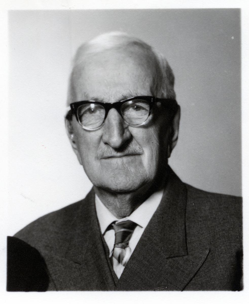 Halvportrett av mann med dress, skjorte, slips og briller.