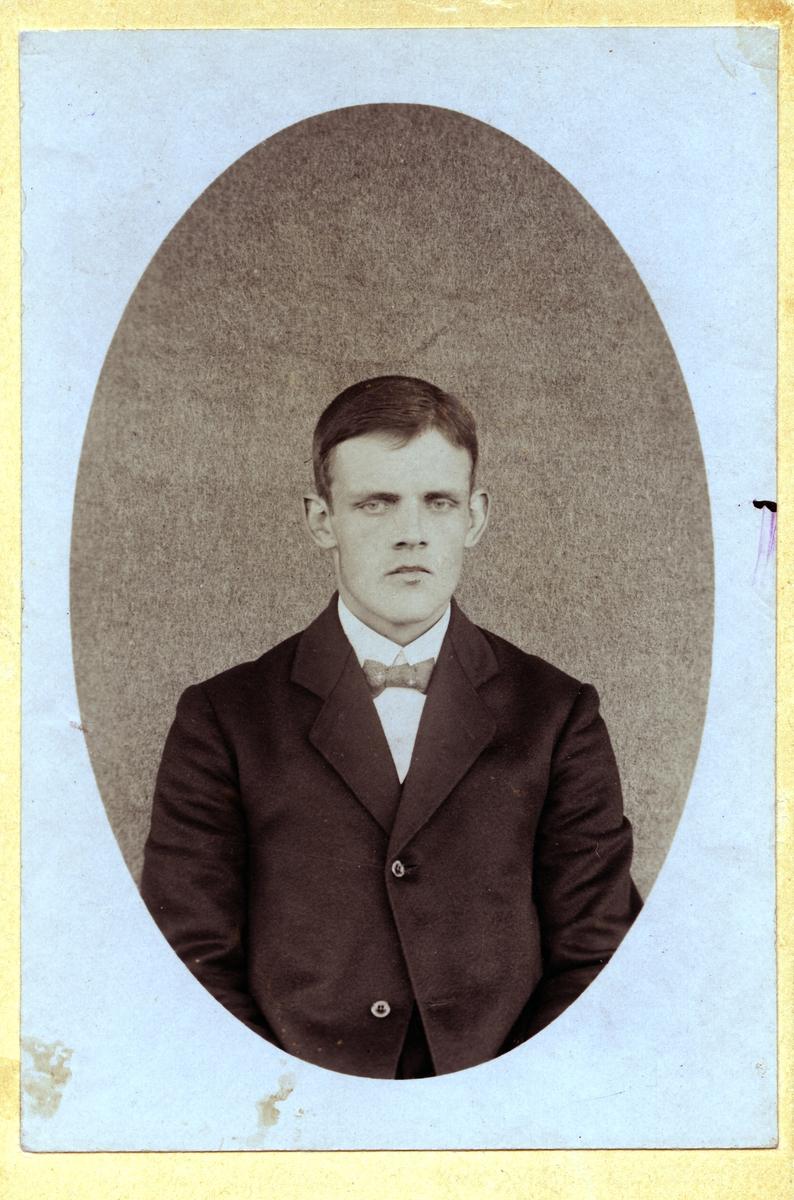 Ung mann avbildet i halvfigur. Han har på seg dress, skjorte og sløyfe