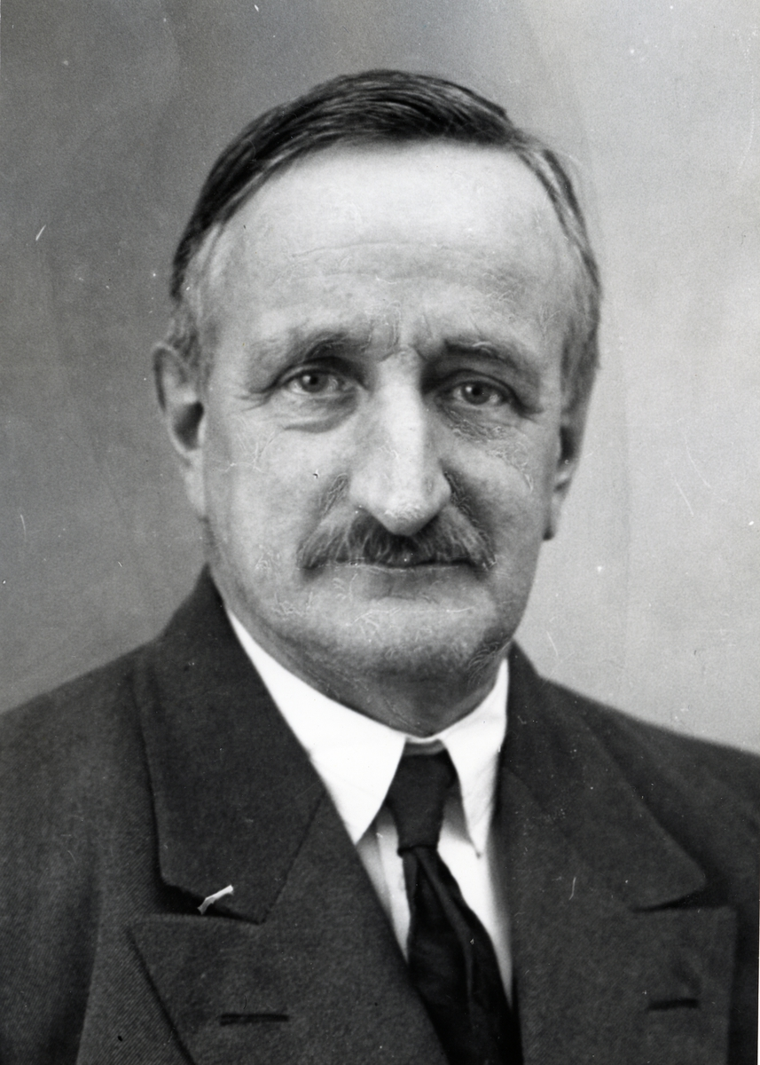 Portrett av mann med dress, hvit skjorte og slips.