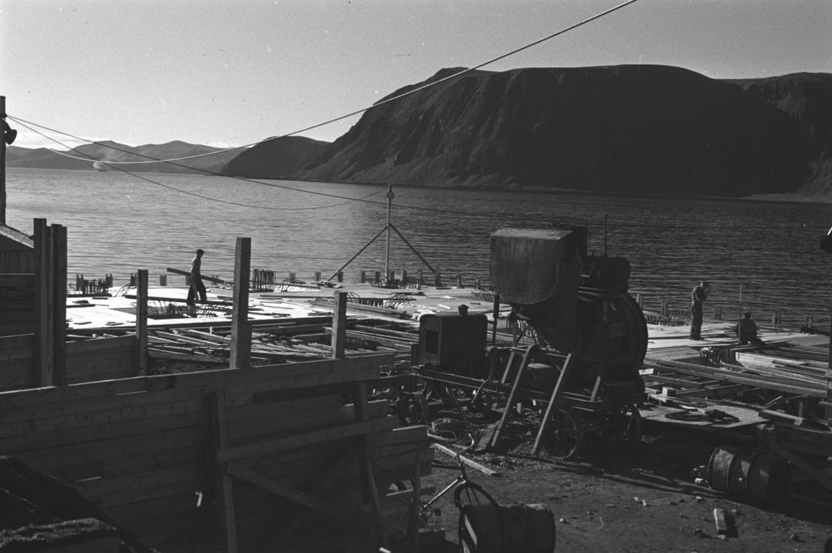Flere anleggsarbeidere bygger en ny kai i Honningsvåg like etter andre verdenskrig.  Ola Hanche-Olsen som har tatt bildene er født 13. mars 1920 i Borre, død 11. februar 1998 i Gjettum. Han var arkitekt og barnebokforfatter. Han hadde artium fra 1939, arkitekteksamen fra NTH 1946 og arbeidet deretter ved Finnmarkskontoret 1946–48 før han etablerte egen arkitektpraksis. Han debuterte som barnebokforfatter i 1974 med lettlestboka Knut og sjørøverne, og skrev i alt 12 bøker. Han var XU-agent 1944-45, og var også en aktiv fjellklatrer og friluftsmann. Ola var gift med Solveig Hanche-Olsen (f. Falkenberg); de fikk 3 barn, blant dem matematikeren Harald Hanche-Olsen.  Arkitektene Solveig og Ola Hanche-Olsen arbeidet ved Brente Steders Reguleringskontor i 1946. Hovedadministrasjon for gjenreisning av Nord-Troms og Finnmark ble lagt til Harstad og fikk navnet Finnmark kontoret. Landsdelen Nord-Troms og Finnmark blev oppdelt i syv distrikt med hver sin administrasjon. Honningsvåg, distrikt IV, skulle betjene Nordkapp, Lebesby, Porsanger og Karasjok kommune