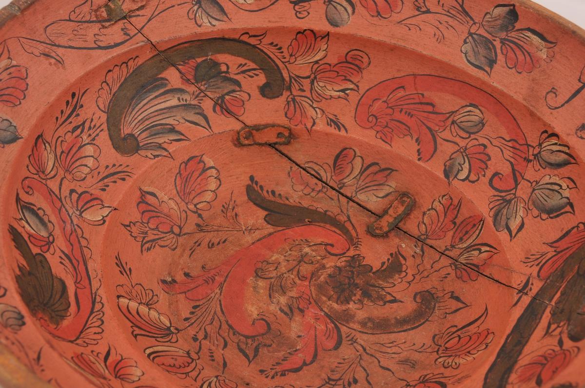 På raud/rosa botnfarge er det rosemåla med farger i grønt, raudt, kvitt og svart. Svarte kantstrekar. Nederst i botnen: akantusranke med blomster, knopper og blad. Neste felt har c-motiv med blomsterrankar. Øvre kant: bord med enkle rankar og lauv.