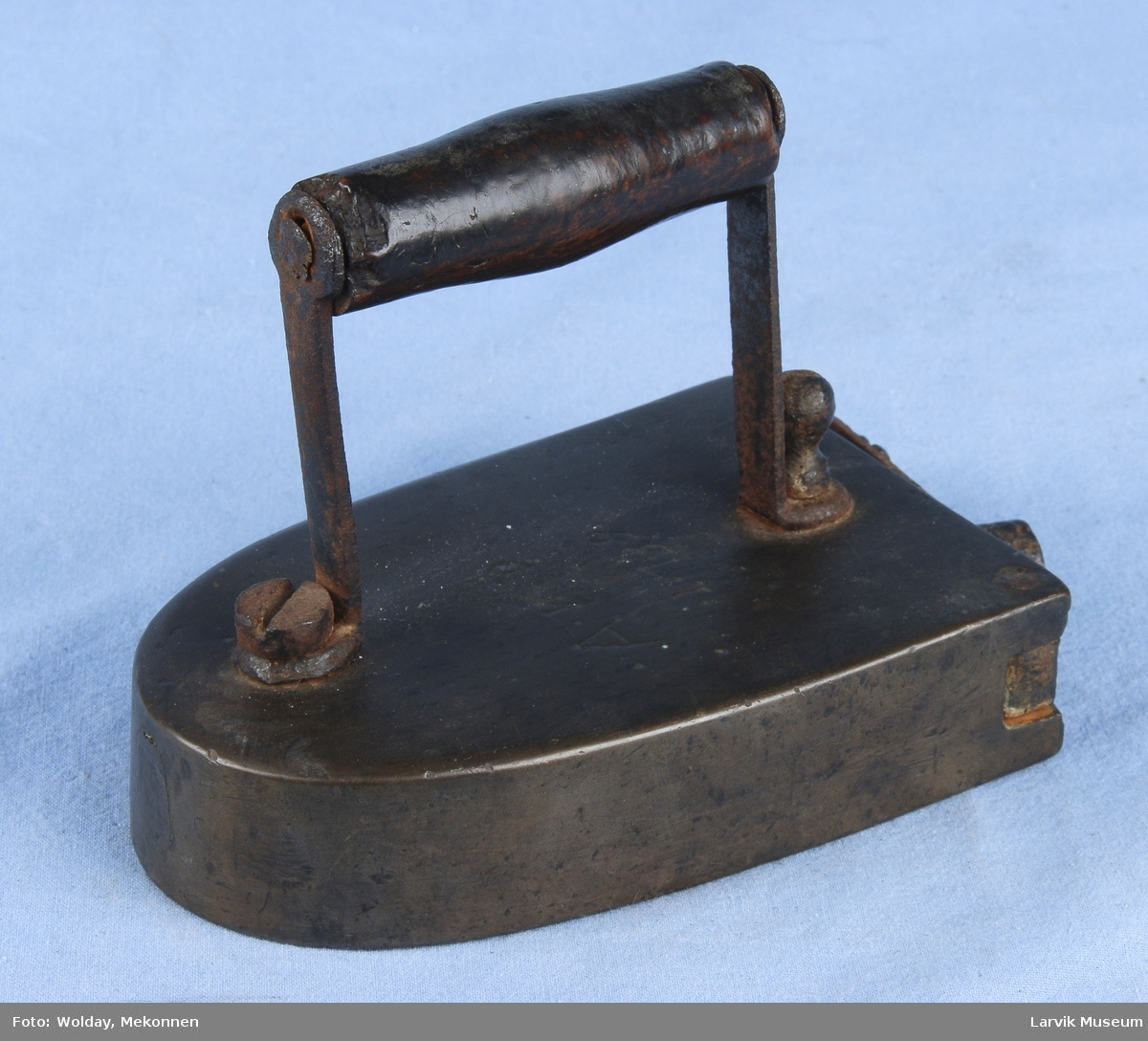 Form: avrundet spiss. hengslet dør bak for ilegg. jerbelastet lås. trehåndtak med støtter i jern fsatskrudd til jernet.