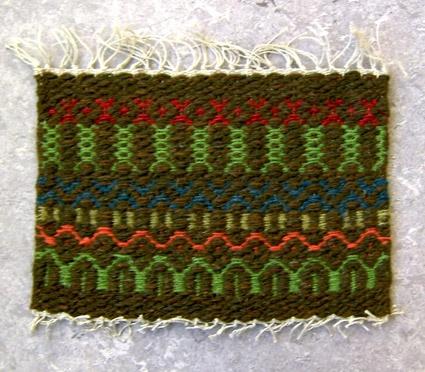 Mattprov i rosengång. Linnemattvarp med inslag av nöthårsgarn i mörkbrunt, grönt, rött, blått och orange.Varpen bildar en ca 4cm lång frans på ena sidan.Provet är från Anna Hådells tid som föreståndarinna, 1961-1975, eller senare.