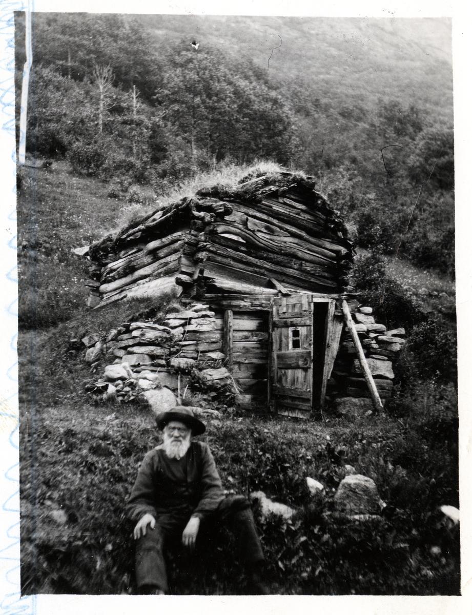 Eldre mann med hvitt skjegg sitter utenfor en gammel, falleferdig låve og fjøs, bygget i bratt terreng.