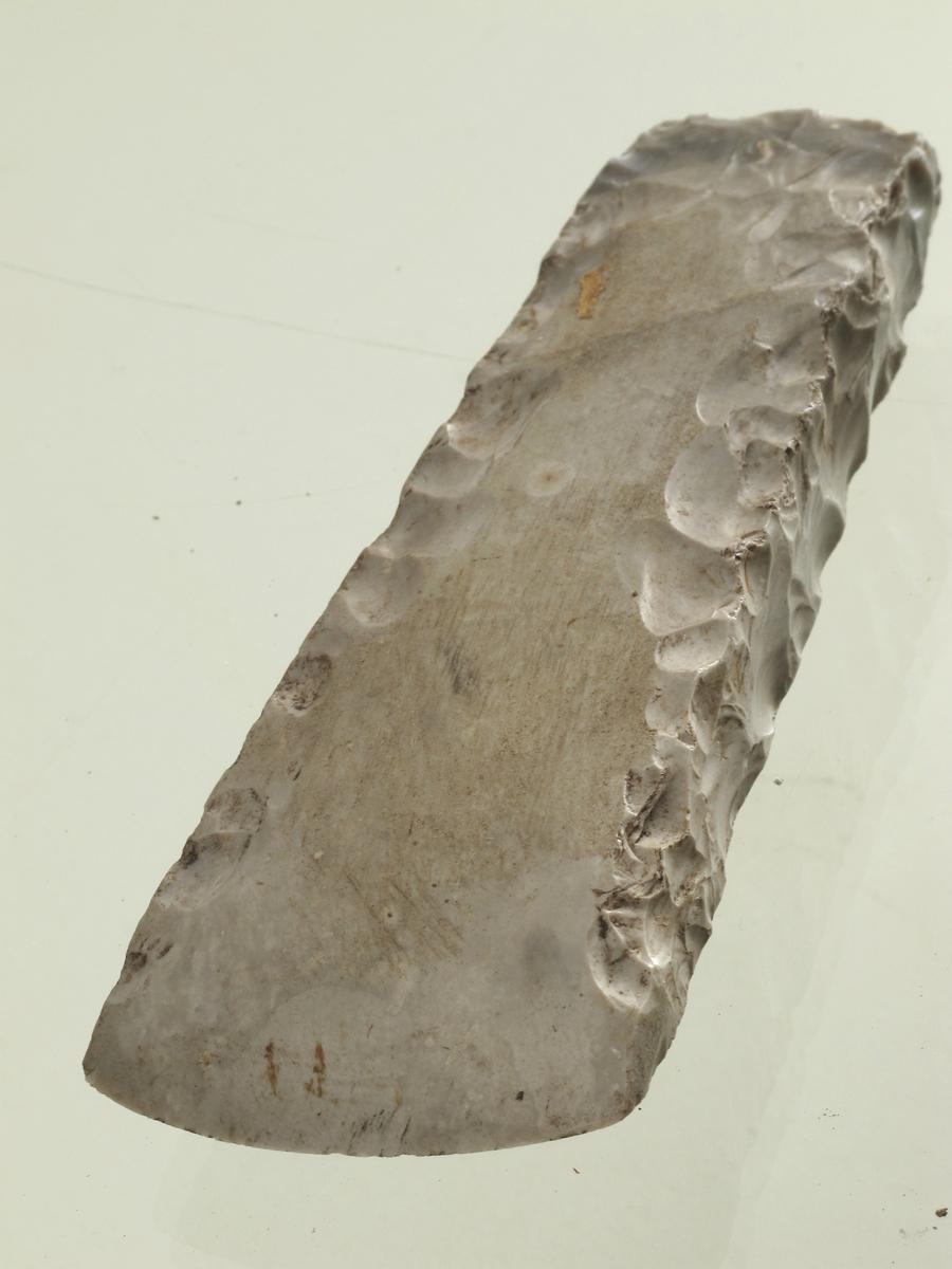 Bredegget øks av lys grå flint av typen [Rygh fig.20]R. 20, bredsidene slipt, men med huggearr langs sidekantene og ved nakken. Smalsidene uslipt. Meget godt bevart.
