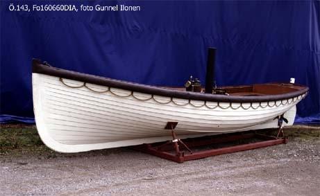 Livbåt Byggd år 1872. Klinkbyggd ångslup i mahogny. Föremålets form: Plattgattad. Ångslupen har 4 tofter, för-och aktertoft. Längsgående sittbräden akter.  Relingen är från för till akter skyddad  av kraftig stoppad avbärare av läder, längsgående livlinor, 4 st åror, 1 roder. I mitten öppen ångmaskin. Skylt i akter: 243 Patent steamlife boat launch built by John Samuel White Cowes. Ångmaskin med skorsten. Panna och maskin märkta G.E. Beliss  & Co Engineers and boiler makers  Birmingham. Pannan dessutom märkt med: No 8    4 1/2