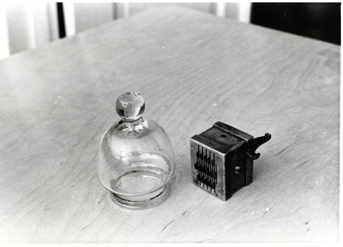 En såkalt smellert liggende på et bord. Ved siden av en glassbeholder.