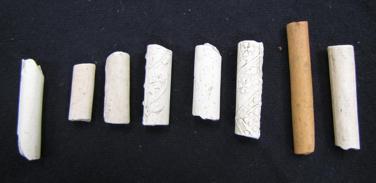 BRÄTTE. LUNDBERG. HUSET UNDER BERGET.  Kritpipskaft, 8 fragment.  År 1943 utförde arkeolog Erik B. Lundberg från riksantikvarieämbetet en arkeologisk utgrävning av den forna staden Brätte.