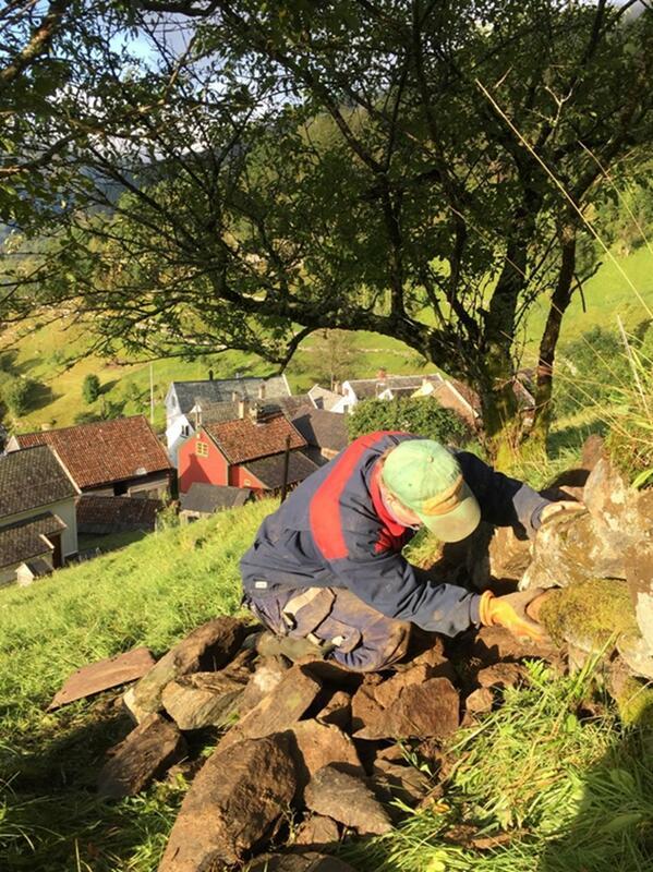 mann arbeider med steinmur i solskin, ovanfor ei samling med gardshus (Foto/Photo)